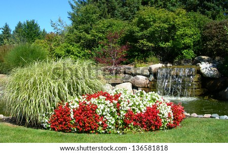 Landscape background with red and white mixed flower beds blossoming against green tall grass with a waterfall background
