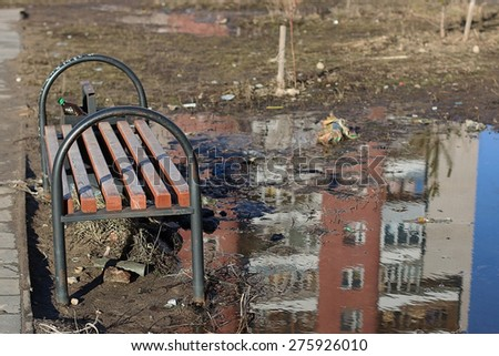 landscape bench in the city around the garbage and puddles with reflection - stock photo