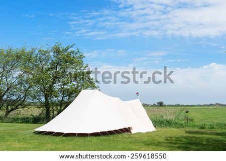Landscape Camping with tent in meadows with sheeps - stock photo