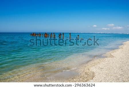landscape, coastline, destroyed rusty pier, the contrast between nature and human activities - stock photo