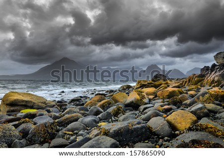 Landscape coastline view of rocks and Cullin hills, Scotland, United Kingdom - stock photo