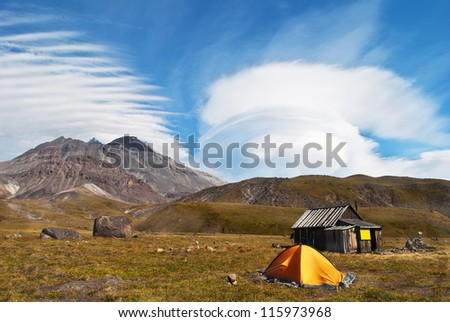 landscape consisting of a blue sky, clouds, mountains and yellow tent. Kamchatka located - stock photo