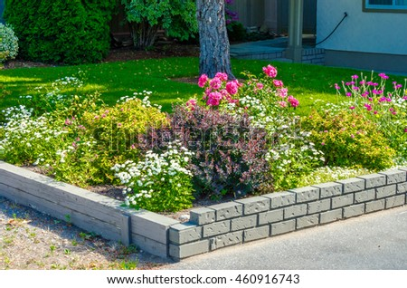 Landscape design. Flowers, stones and nicely trimmed yard and bushes in front of the house, front yard.