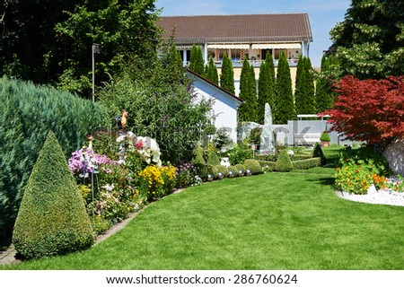 landscape design. Garden with green grass and flowers near cottage - stock photo