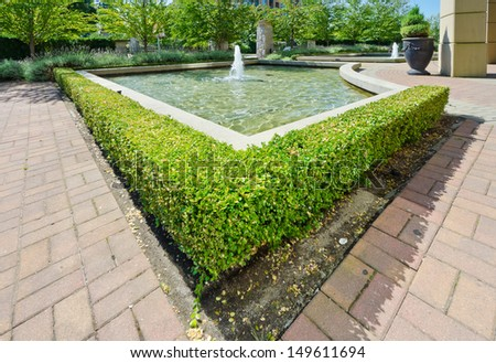 Landscape design. Nicely trimmed bushes  around fountain in the park. Vancouver. Canada.