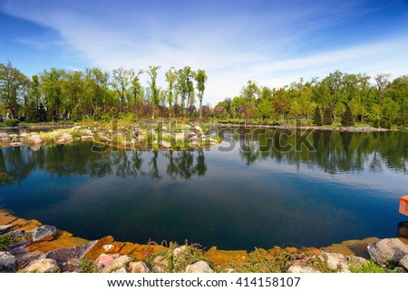 Landscape design. Pond in park with trees and stones. Blue sky reflected in water