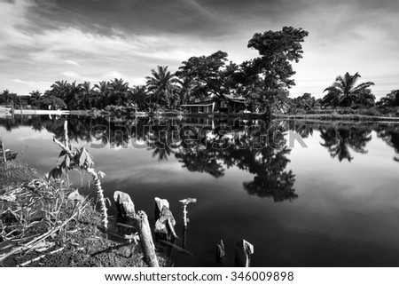 Landscape during daytime with river reflection of rural house and tree in black and white format. - stock photo