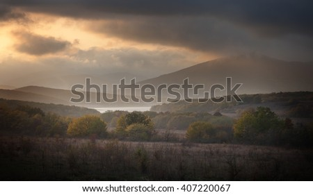 Landscape. Forest and mountains in the clouds at sunset
