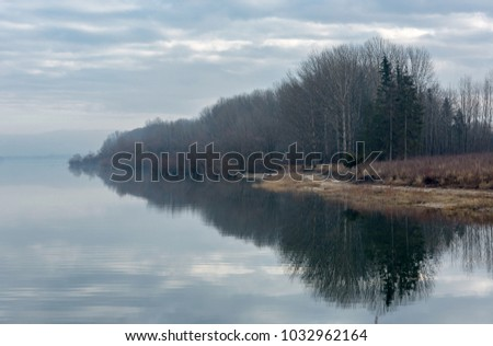 landscape forest with water reflection on mountain lake shore