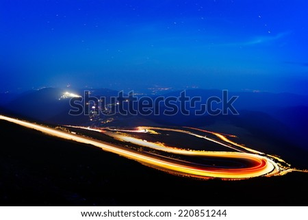 Landscape from the rocky Fagaras mountains in Romania in the summer evening with Transalpina winding road in the distance - stock photo