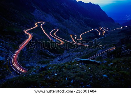 Landscape from the rocky Fagaras mountains in Romania in the summer evening with Transfagarasan winding road in the distance - stock photo