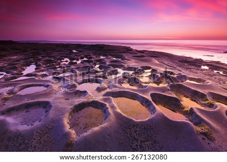 Landscape full of craters in vibrant colors of pink and red - stock photo