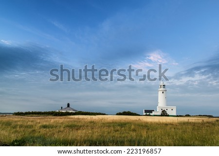 Landscape image large Summer sky with lighthouse in distance