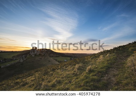 Landscape image of enchanting fairytale castle ruins during beautiful sunset