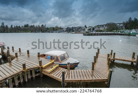 Landscape image of Lake Windermere in Lake District, a National Park in England, during Autumn with grey sky, and colourful boats next to jetty - stock photo