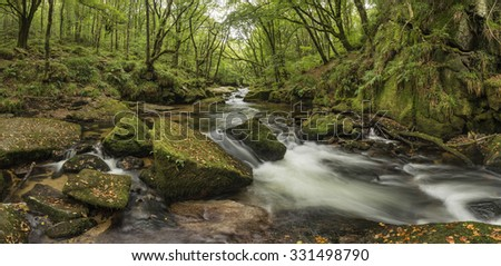 Landscape image of river flowing through lush green forest in Summer - stock photo