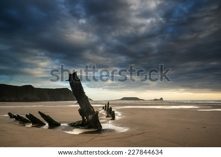 Landscape image of shipwreck on beach at sunset in Summer - stock photo