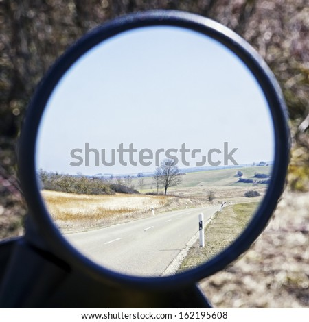 landscape in a rear mirror of a motorbike - stock photo