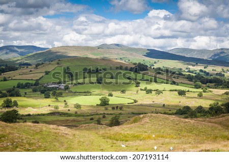 Landscape in Cumbria, UK, with sunlight breaking through clouds, creating beautiful patches of light - stock photo