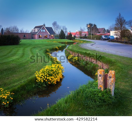 Landscape in dutch village with beautiful house reflected in water canal, courtyard with green grass , yellow flowers and road with illumination at dusk in Netherlands. - stock photo