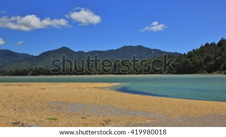Landscape in the Abel Tasman national park. Awaroa Inlet. Sandy beach, blue water and green hills. - stock photo