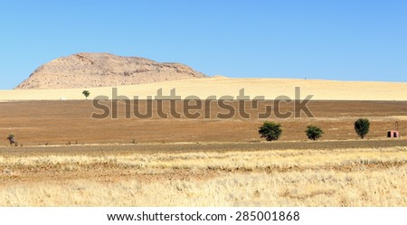 Landscape in The Namib-Naukluft National Park. Namib-Naukluft  is a national park of Namibia encompassing part of the Namib Desert (considered the world's oldest desert) and the Naukluft mountains. - stock photo