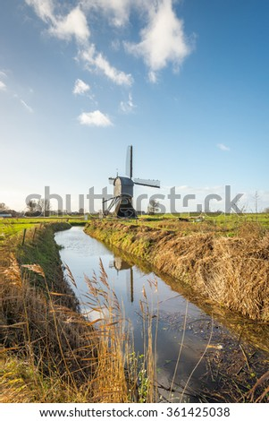 Landscape in the Netherlands with a historic wooden hollow post mill and a narrow stream with a reflecting water surface. It's a sunny day in autumn and the reed plants are yellowed.  - stock photo