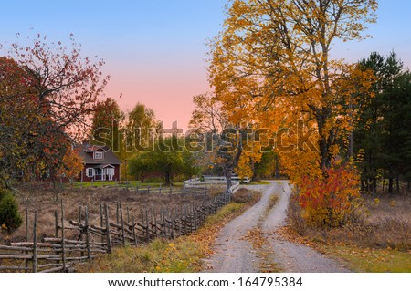 Landscape in the province of Smaland in the south east of Sweden. Typical view with dirt road and wooden fences and in the background a red wooden house - stock photo