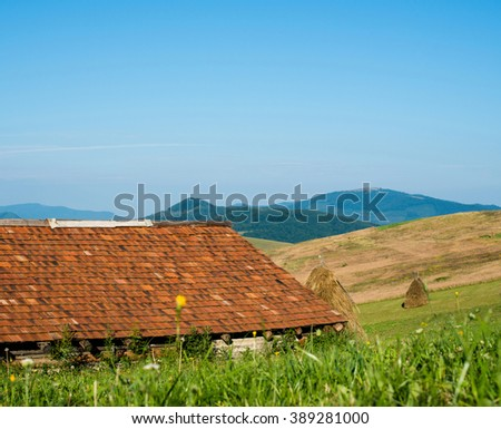 Landscape in the Ukrainian Carpathian Mountains. Wooden house with orange tiled roof in the foreground, - stock photo
