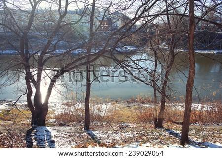 landscape late autumn sun freezing river park - stock photo
