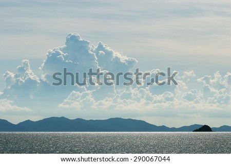 Landscape light reflected from the surface of the sea. Beautiful clouds and mountains, far away. - stock photo