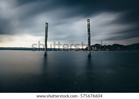 Landscape long exposure shot with water surface and two port wooden poles. Sky is dark with clouds and looks stormy. In background is small town with church tower and two small rock wall on the right.