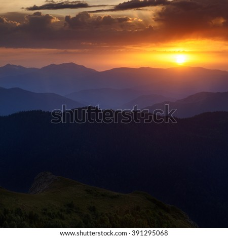 Landscape. Mountain ridges at sunset against the sky with clouds