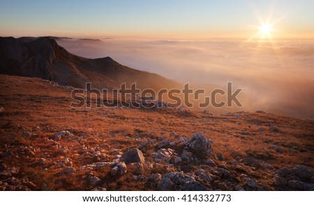 Landscape. Mountain slopes in the mist at sunrise