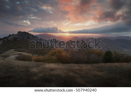 Landscape. Mountain slopes in the mist at sunset