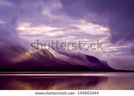 Landscape. Mountains and lake in mist in morning with purple col - stock photo
