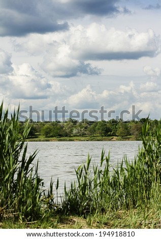 Landscape. Nature, on the shore of the lake is rich greens and sky reflected in water - stock photo