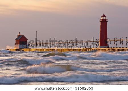 Landscape near sunset of Grand Haven, Michigan lighthouse, Lake Michigan, on a blustery day - stock photo