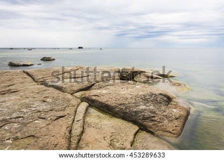 Landscape of a large brown rocks in the sea at a cloudy day