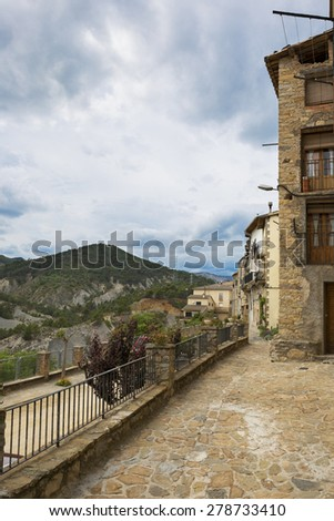 landscape of a medieval village, street view with mountains in the background, cloudy sky. Catalonia, Spain