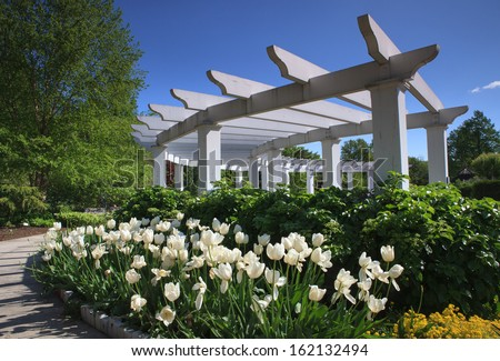 Landscape of an outdoor arbor with spring flowers against a blue sky at Hershey Gardens in Pennsylvania