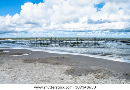 Landscape of beach and sea with waves, cloudy sky. Baltic sea coast near Leba in Poland. - stock photo