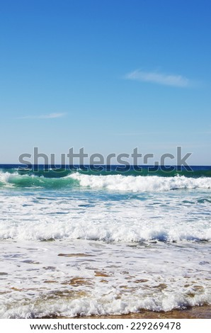 landscape of beach with green water and blue sky - stock photo
