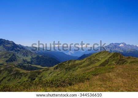 landscape of blue sky and green grass of alpine meadows with rocky mountains valley far away in Caucasus mountains Abkhazia Georgia - stock photo
