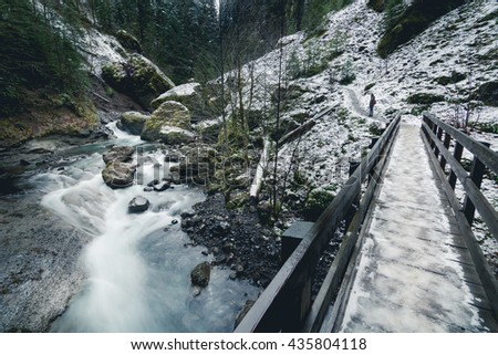 Landscape of Columbia River Gorge, Oregon, United States. This landscape of Oregon is at the trail to Wahclella Falls. This landscape has a trail, river flows, snow, forest, and woman tourist. - stock photo