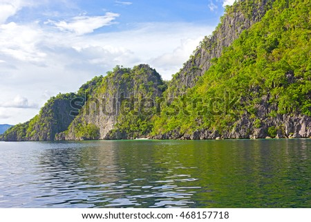 Landscape of Coron Island with a small white sand beach, Philippines. Steep hills on the tropical island
