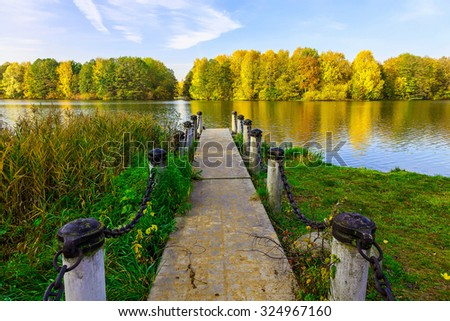 Landscape of Dock and Autumn Shoreline with Colourful Trees of Lake in the Afternoon - stock photo