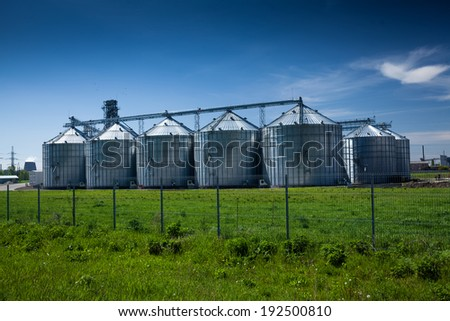Landscape of grain elevator at field against deep blue sky - stock photo
