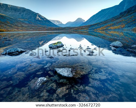 Landscape of lake Tahtarjavr with transparent water, rocky bottom and distant mountains reflected in still morning waters, Hibiny mountains above the Arctic circle, Russia - stock photo