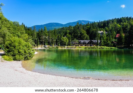 Landscape of lakeside with green water, trees and mountains. - stock photo